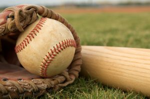 A baseball in a glove and a baseball bat lying on grass